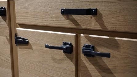 Finte maniglie e scatto che affidano la chiusura dell'anta al veccuio sistema a scatto con rotellina (!)